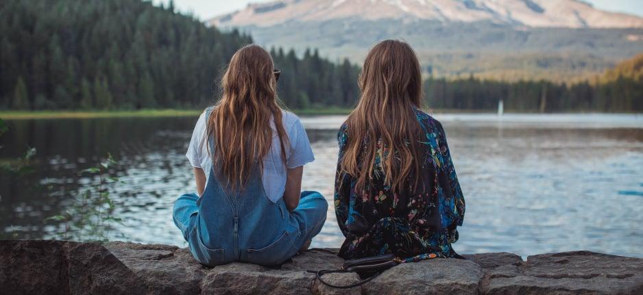 two girls sitting by lake