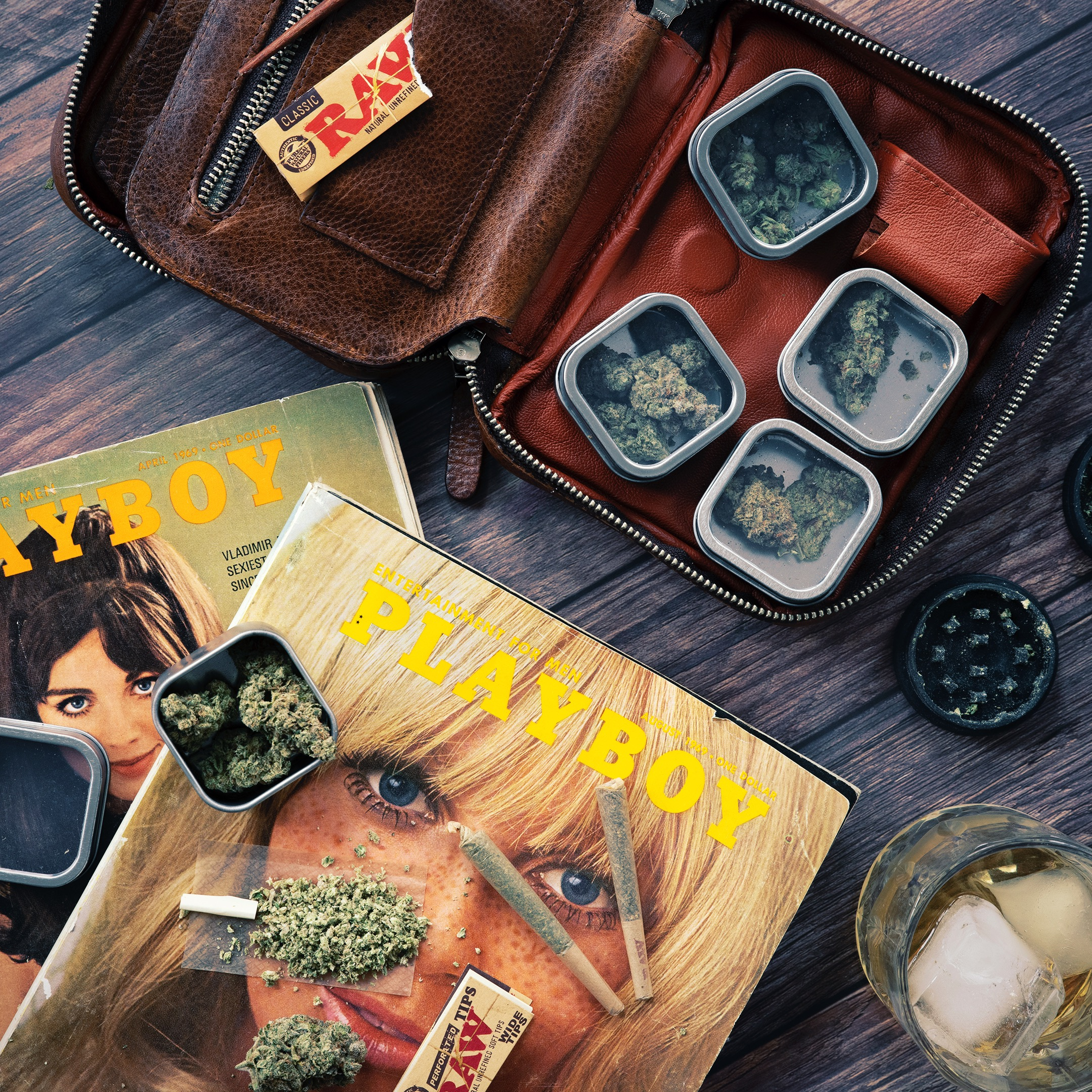 leather traveling case with cannabis next to vintage playboy magazines