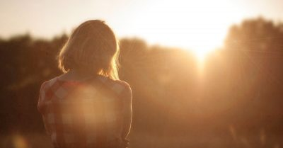 silhouette of woman with sun shining
